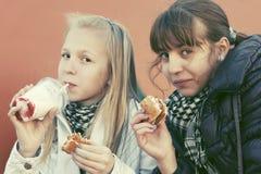 Consumición adolescente de las muchachas hamburguesas en el café de la acera Fotografía de archivo