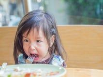 Consumición asiática del niño de la muchacha foto de archivo