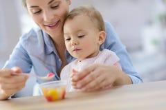 Consumición de ayuda de la madre joven a su bebé Imagen de archivo libre de regalías