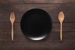 Consumición de concepto Cuchara, bifurcación y plato negro en el backgro de madera Foto de archivo