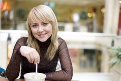 Consumición de la muchacha rubia con la cuchara en restaurante Imagenes de archivo