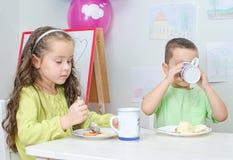 Consumición de la niña y del muchacho Foto de archivo libre de regalías