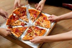 Consumición de la pizza Grupo de amigos que comparten la pizza Alimentos de preparación rápida, ocio foto de archivo