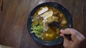 Consumición de la sopa de fideos asiática Laksa Visión superior almacen de video