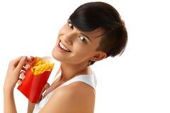 Consumición de los alimentos de preparación rápida Muchacha que come las patatas fritas Nutrición lifestyle foto de archivo libre de regalías