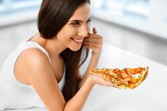 Consumición de los alimentos de preparación rápida Mujer que come la pizza italiana Nutrición Dieta, L foto de archivo