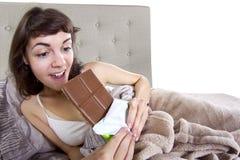 Consumición de los bocados en cama Fotografía de archivo libre de regalías