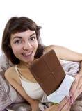 Consumición de los bocados en cama Imagenes de archivo