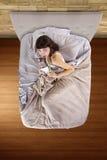 Consumición de los bocados en cama Foto de archivo libre de regalías