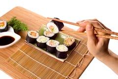 Consumición de los rollos de sushi Fotos de archivo libres de regalías
