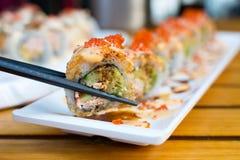 Consumición de los rollos de sushi con los palillos Foto de archivo libre de regalías