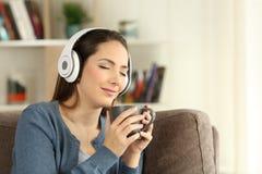 Consumición de relajación de la mujer y el escuchar la música Imagen de archivo