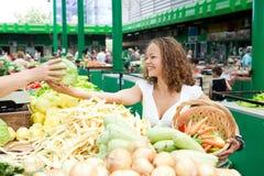 Consumición de serie: Col de compra de la mujer joven en el mercado del ultramarinos Foto de archivo libre de regalías