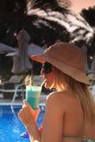 Consumición de un coctel por la piscina Imagen de archivo