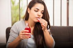 Consumición de un poco de jarabe de la tos Foto de archivo