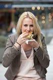 Consumición de una hamburguesa Imagen de archivo libre de regalías