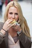 Consumición de una hamburguesa Imagenes de archivo