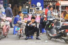 Consumición del alimento del vendedor ambulante en China Foto de archivo libre de regalías