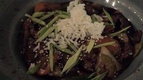 Consumición del arroz y del plato asiático vegetal en el restaurante almacen de video