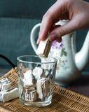 Consumición del caramelo del turrón en un vidrio y una caldera, manos Imagen de archivo