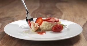 Consumición del pastel de queso de la fresa con la bifurcación en la tabla de madera Fotografía de archivo