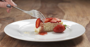 Consumición del pastel de queso de la fresa con la bifurcación en la tabla de madera Fotografía de archivo libre de regalías