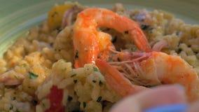 Consumición del risotto con el calamar y las gambas en restaurante del marisco metrajes