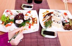 Consumición del sushi con los palillos Imagen de archivo