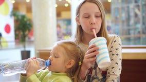 Consumición divertida del niño del retrato lindo de las muchachas en zona de restaurantes rápida en una alameda