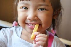 Consumición feliz de la muchacha asiática linda Fotografía de archivo libre de regalías