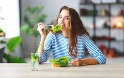 Consumición sana chica joven feliz que come la ensalada por mañana en cocina imágenes de archivo libres de regalías