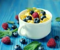 Consumición sana, comida y concepto de la dieta - copos de maíz con las bayas fotos de archivo