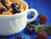 Consumición sana, comida y concepto de la dieta - copos de maíz con las frambuesas y los arándanos de las bayas en fondo de mader imágenes de archivo libres de regalías