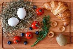 Consumición sana con los huevos, la fruta de kiwi y un cruasán Foto de archivo libre de regalías