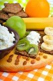 Consumición sana Fruta fresca, copos de maíz y panes secos con la cuajada Imagen de archivo