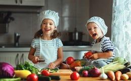 Consumición sana Los niños felices preparan la ensalada vegetal en kitc foto de archivo libre de regalías