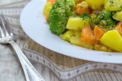 Consumición sana Patatas cocidas al vapor de las verduras, zanahorias, bróculi, maíz con las hierbas frescas Foto de archivo