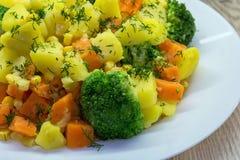 Consumición sana Patatas cocidas al vapor de las verduras, zanahorias, bróculi, maíz y eneldo fresco imagenes de archivo