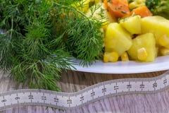 Consumición sana Patatas cocidas al vapor de las verduras, zanahorias, bróculi, maíz y eneldo fresco Foto de archivo