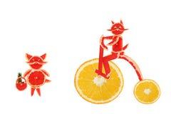 Consumición sana. Pequeños gatos divertidos hechos de las rebanadas del pomelo. Foto de archivo libre de regalías