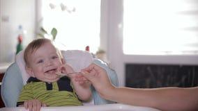 Consumición sonriente linda del bebé, sentándose en el asiento del bebé en casa Mime a alimentar su de un año adorable con una cu metrajes