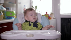 Consumición sonriente linda del bebé, sentándose en el asiento del bebé en casa Mime a alimentar su de un año adorable con una cu almacen de video