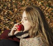 Consumición y manzana de la mujer en otoño Imagen de archivo libre de regalías