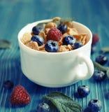 Consumici?n sana, comida y concepto de la dieta - copos de ma?z con las frambuesas y los ar?ndanos de las bayas en fondo de mader imagen de archivo libre de regalías