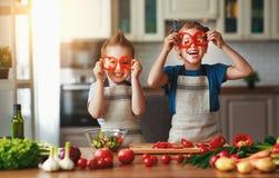 Consumici?n sana Los ni?os felices preparan la ensalada vegetal en cocina imágenes de archivo libres de regalías