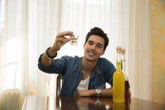 Consumición que se sienta del hombre joven solamente en una tabla, haciendo una tostada Foto de archivo libre de regalías