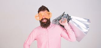 Consumidor adicto que hace compras Concepto total de la venta Inconformista barbudo del hombre con los bolsos de compras de la po imágenes de archivo libres de regalías