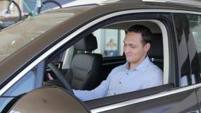 Consumidor que dá os polegares-acima, chaves do carro nas mãos dos homens, homem do prazer, video estoque