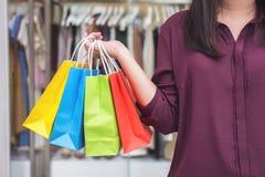 Consumismo, concetto di compera di stile di vita, condizione della giovane donna e sacchetti della spesa variopinti della tenuta  fotografie stock libere da diritti