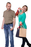 Consumption. Man stands with empty pockets next to a women with filled shopping bags Stock Photography